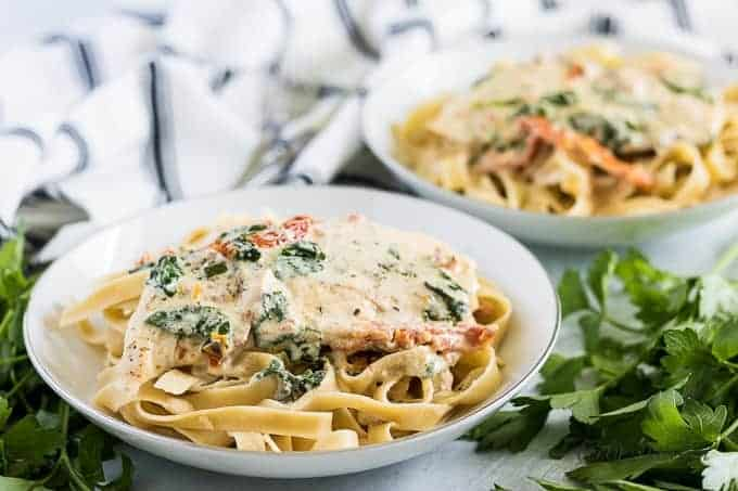 Two plates of Tuscan chicken pasta topped with shredded Parmesan cheese.