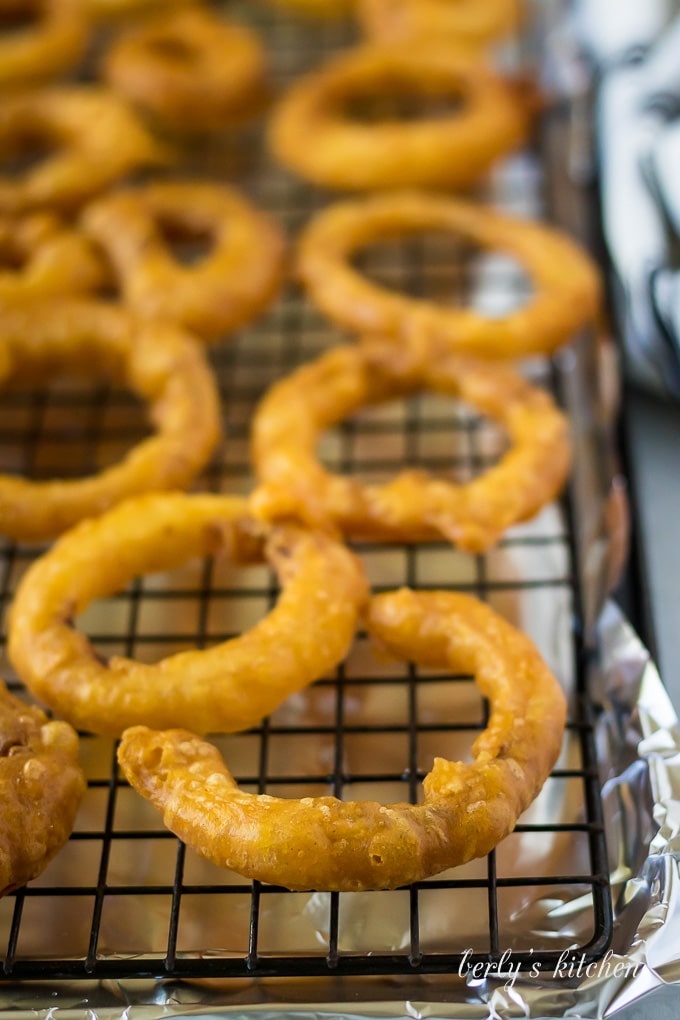 A prepared wire rack with foil holding the fried onion rings.