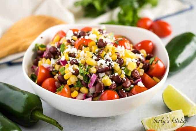 A bowl filled with corn and black bean salsa garnished with limes.