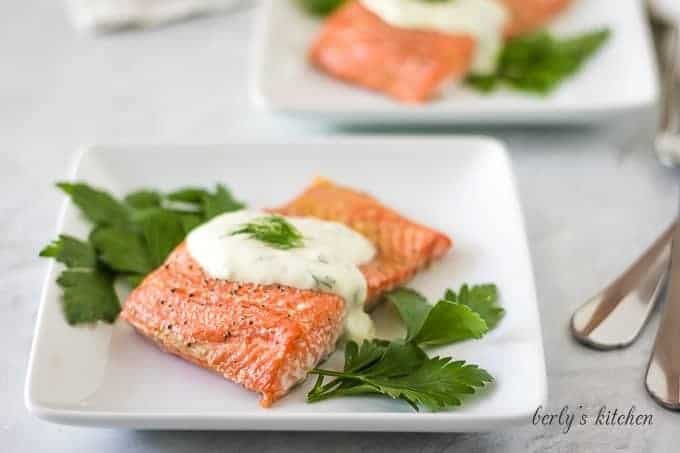The finished baked salmon topped with dill sauce and garnished with parsley.