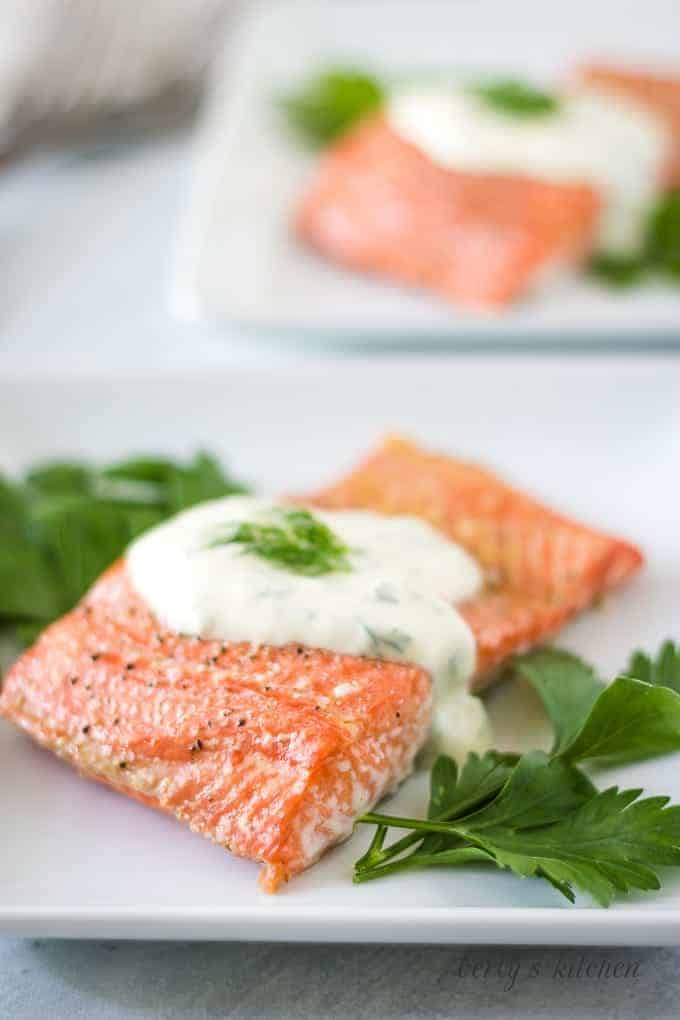 The last photo shows the finished salmon on a plate with sauce.