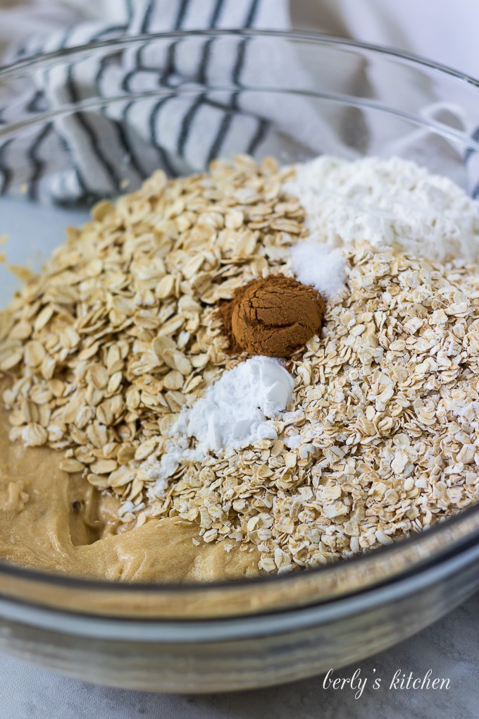 Flour, oats, and other ingredients have been added to the mixing bowl.