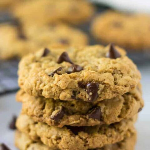 Multiple oatmeal chocolate chip cookies stacked up on each other.