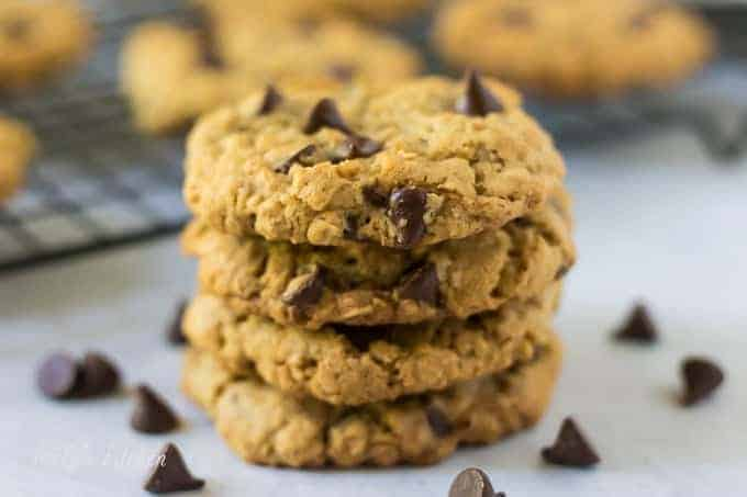 Four stacked oatmeal chocolate chip cookies surrounded by chocolate chips.