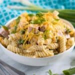 A large, white bowl of the ham and cheese pasta salad.