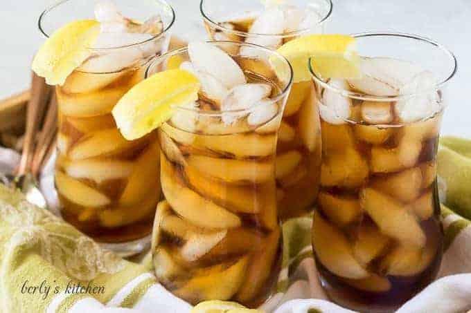 Four glasses of iced tea with lemon.