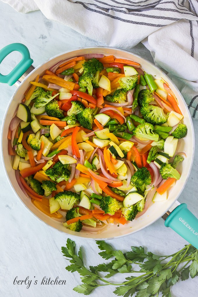 More vegetables have been added to the skillet to cook.