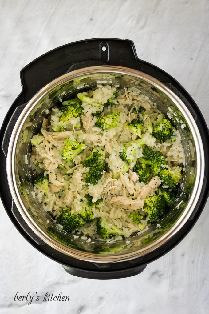 The cooked meat has been shredded and broccoli has been added.