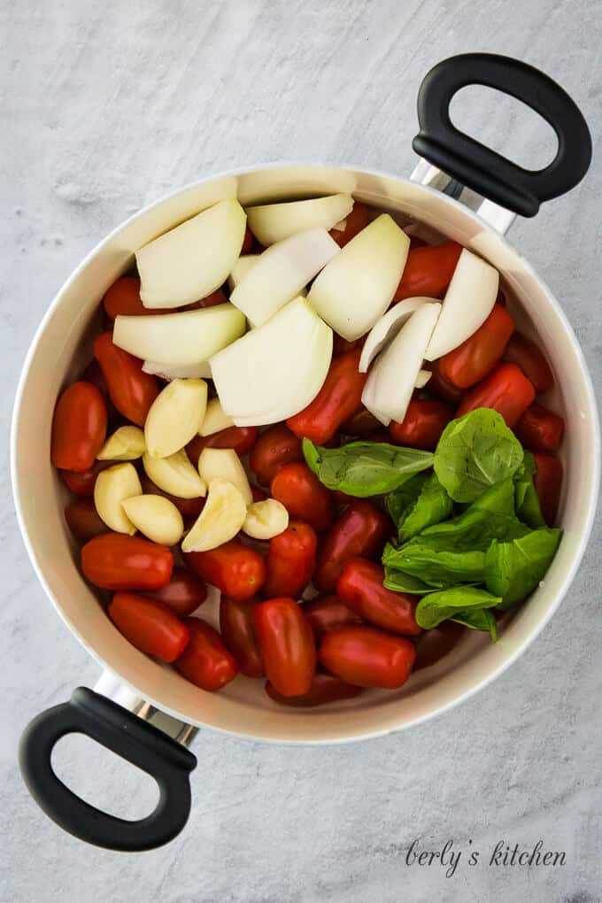 The tomatoes, onions, garlic and other ingredients is a pan.