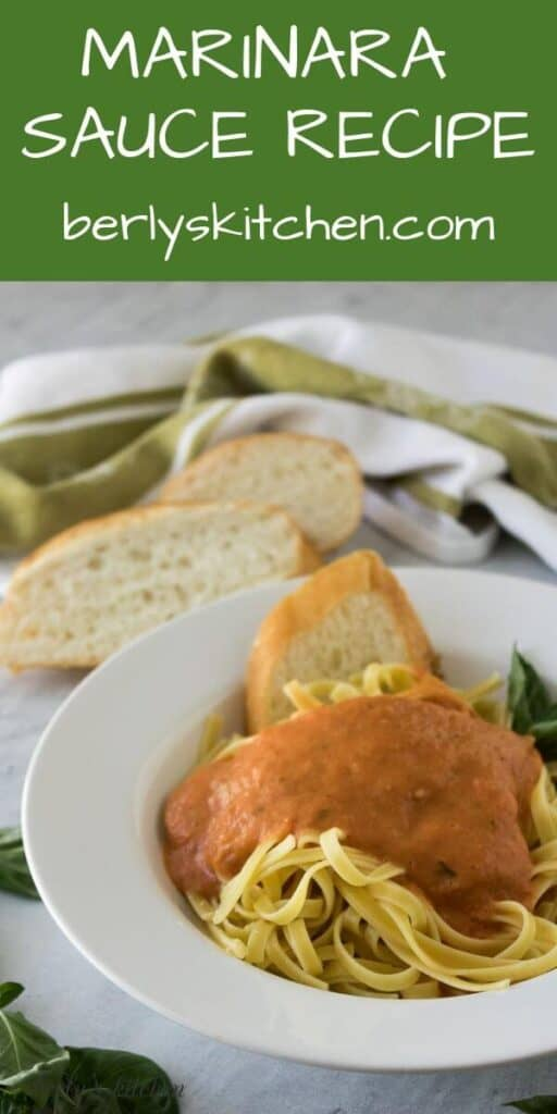 The marinara sauce over a bed of pasta garnished with fresh basil.