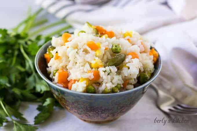 A decorative bowl filled with the pressure cooker rice with vegetables.