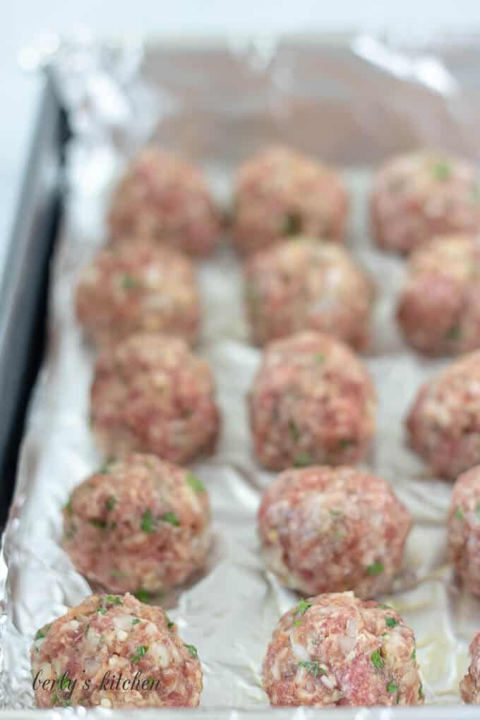 The meatballs have been rolled out and placed on a pan.