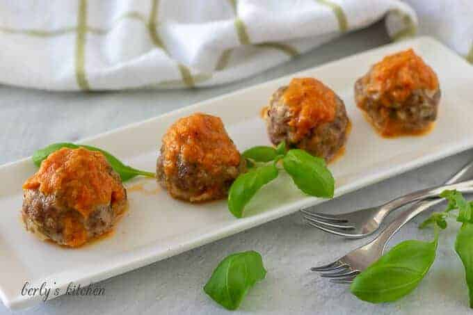 Four oven baked meatballs on a rectangular plate topped with red sauce.