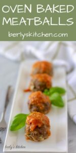 Four sauce topped oven baked meatballs garnished with fresh basil.