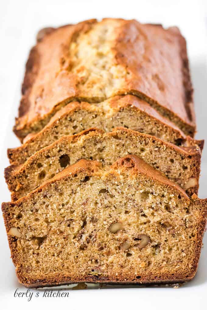 Front facing photo of a loaf of sliced banana bread on a white platter.