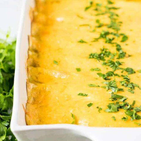 The baked cheesy enchiladas garnished with fresh chopped parsley.
