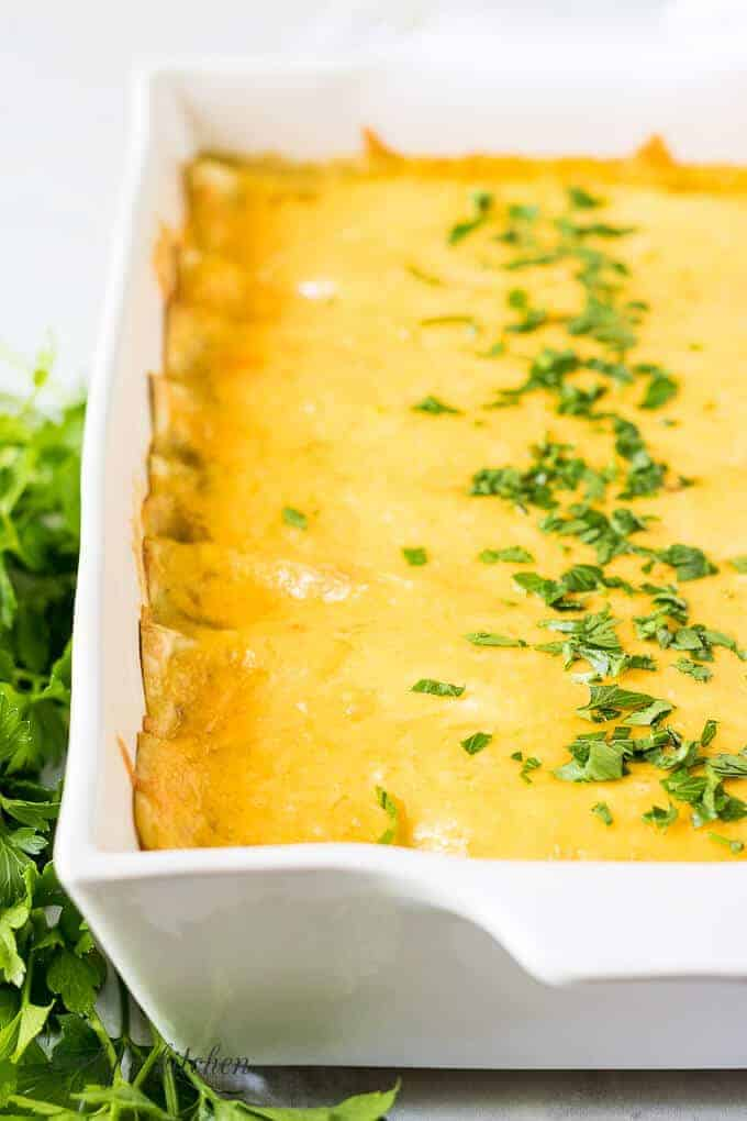 The baked cheesy enchiladas garnished with fresh chopped parsley.