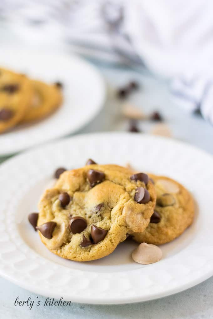Three caramel chocolate chip cookies on a small white plate.