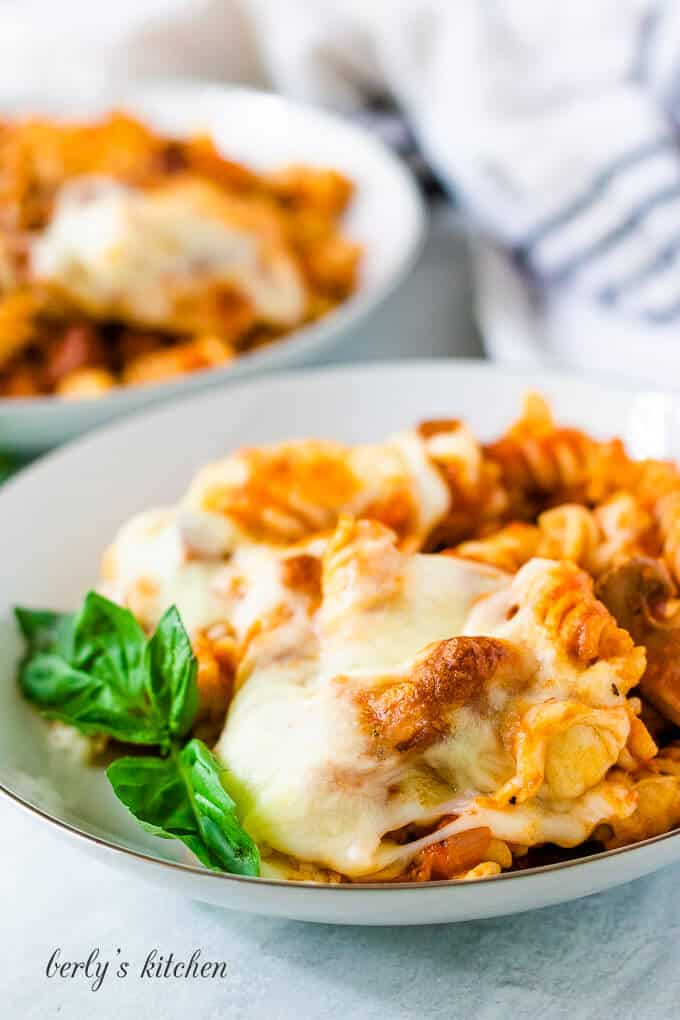 Two bowls of the pasta casserole garnished with fresh basil.