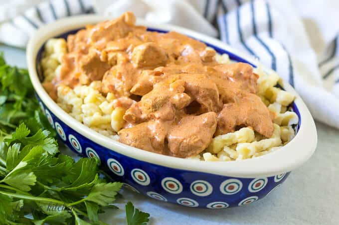 Paprika chicken served on spaetzle in a decorative blue bowl.