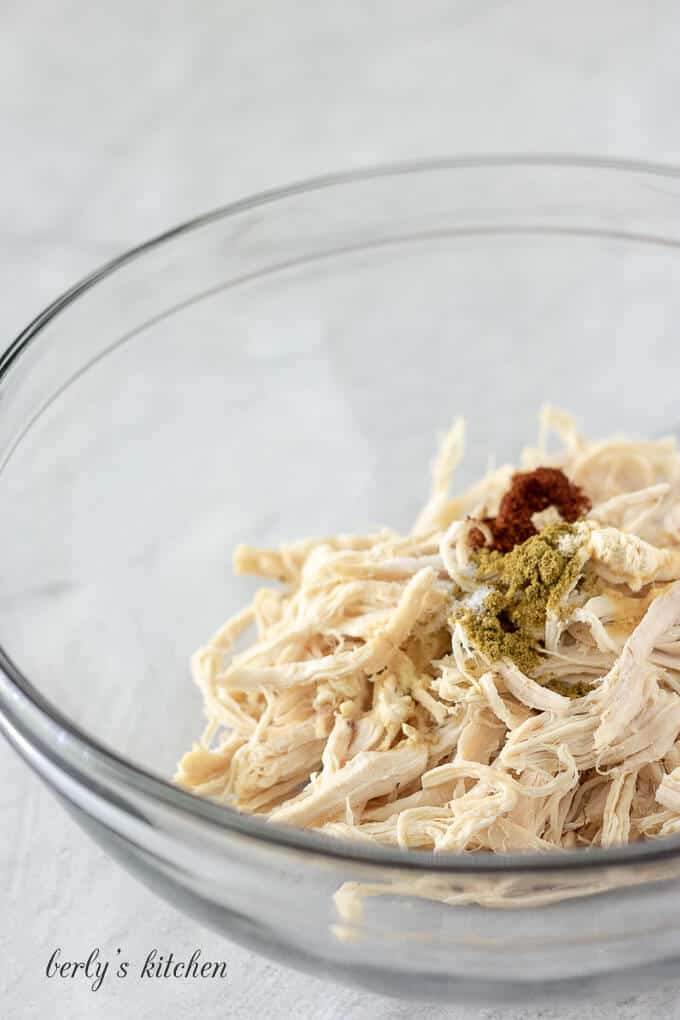 Shredded chicken in a bowl mixed with a blend of spices.
