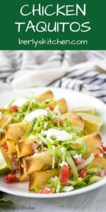 A plate of chicken taquitos served with lettuce, tomatoes, and sour cream.