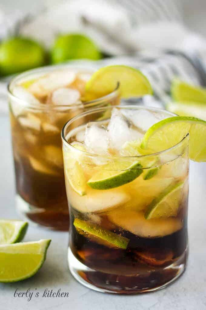 The Cuba libre drink has been garnished with a lime wedge.