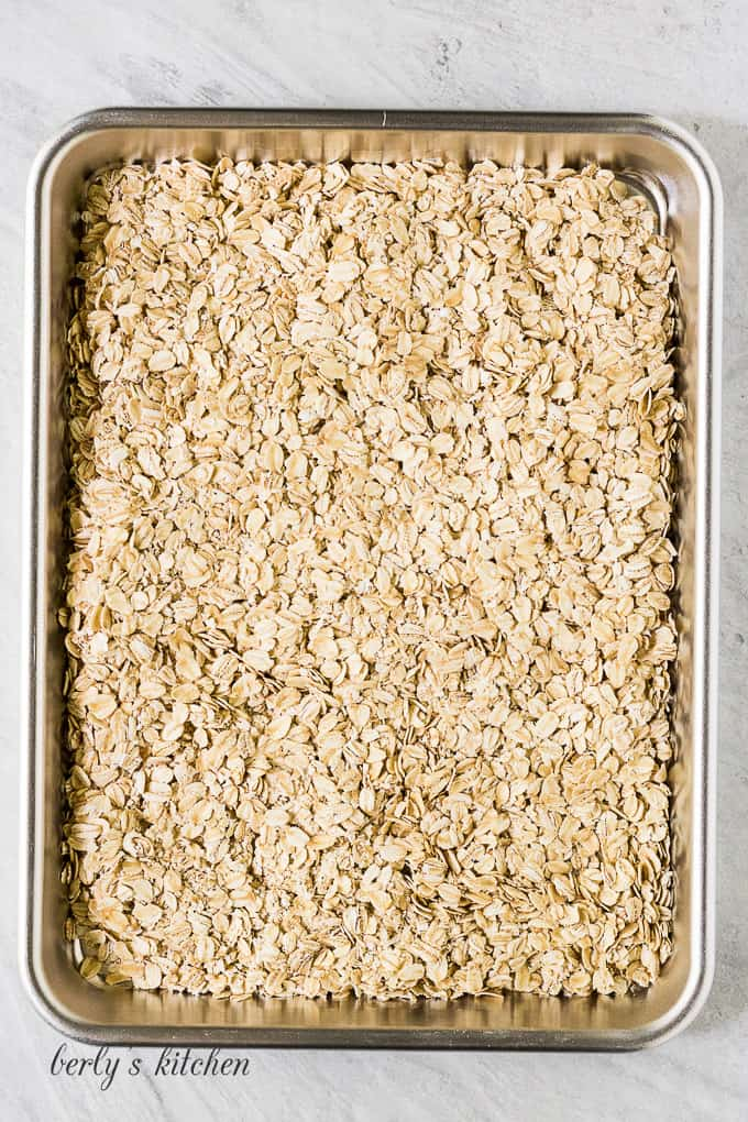 A large metal sheet pan filled with the toasted oats.