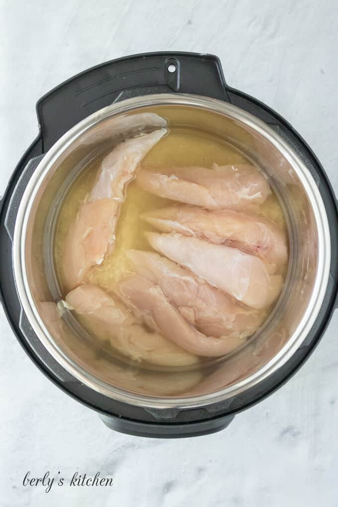 The broth, meat, and rice in the pressure cooker liner.