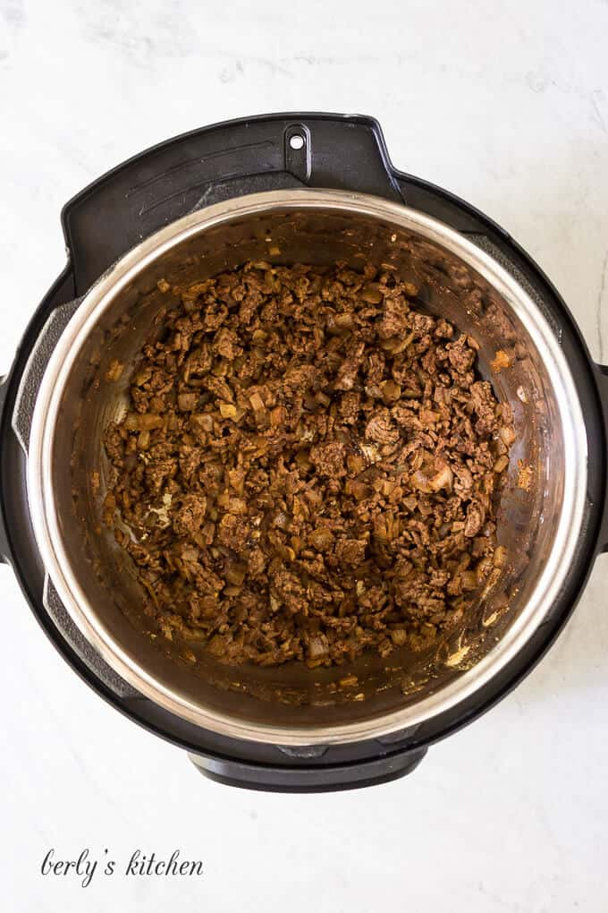 Ground beef, onions, and other ingredients sauteed in the cooker.