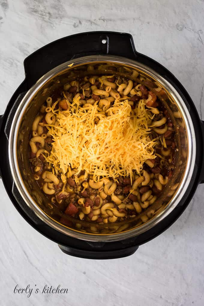 Shredded cheese has been added to finish the chili mac.