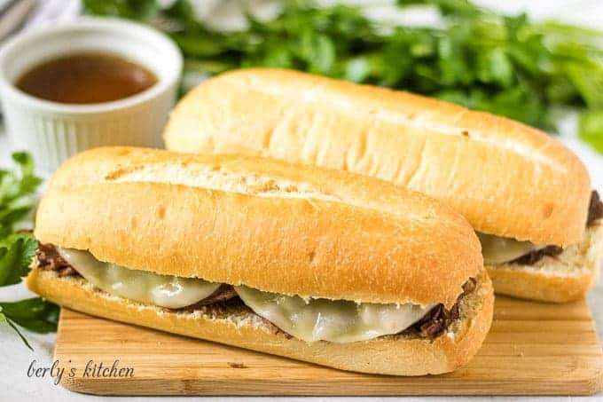 Two Instant Pot French dip sandwiches served with au jus.