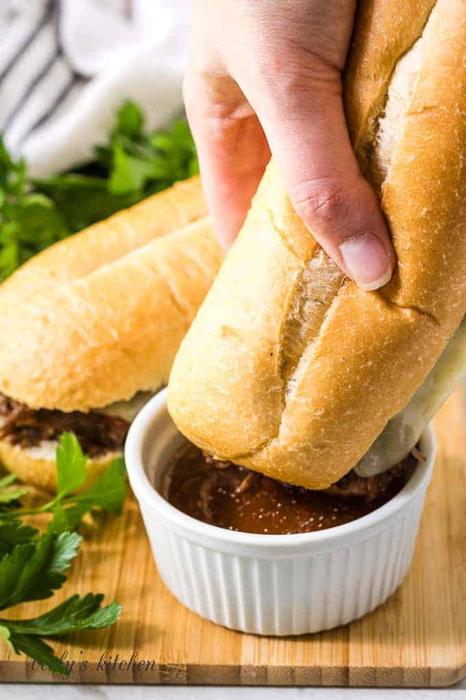 The French dip sandwich being dipped in a side of au jus.