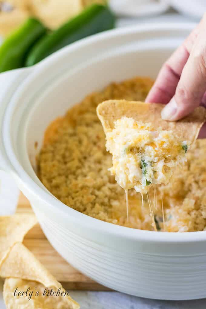 A tortilla chip being dipped into the jalapeno popper dip.
