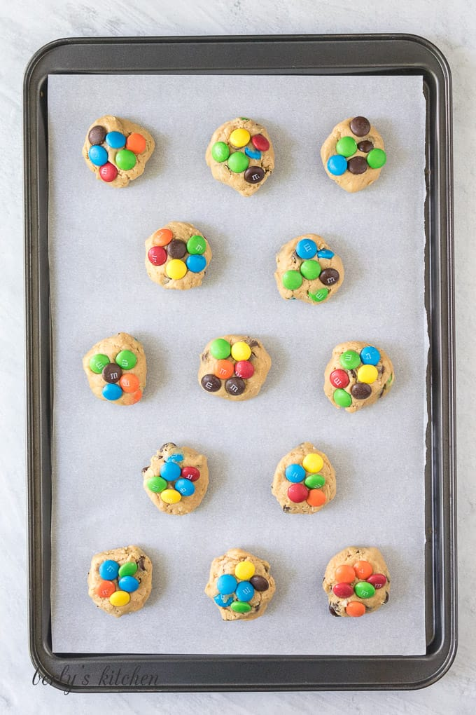 The cookie balls have been placed on a sheet pan.