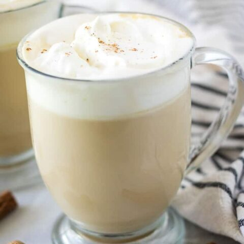 The coffee drink has been garnished with whipped cream and ground cinnamon.