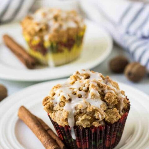 Two muffins, on plates, garnished with a fresh cinnamon stick.