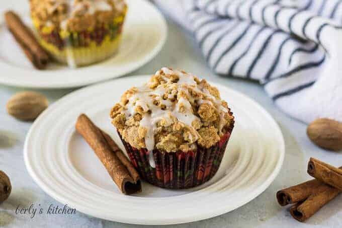 A pumpkin spice muffin on a plate topped with streusel.