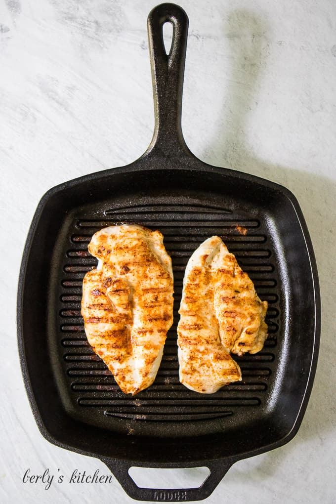 Two large pieces of chicken breast grilling on a griddle.