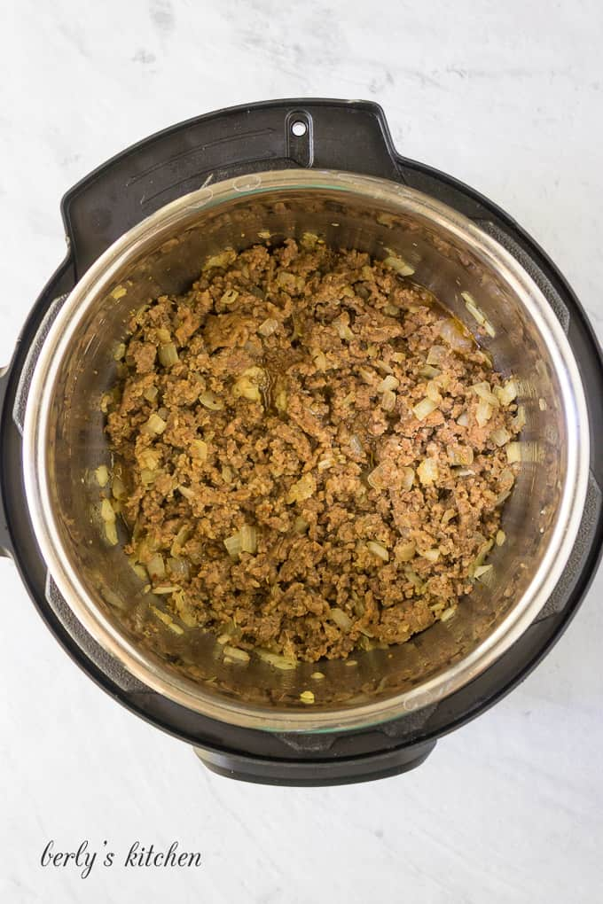 Meat, vegetables, and spices being cooked in the pressure cooker.