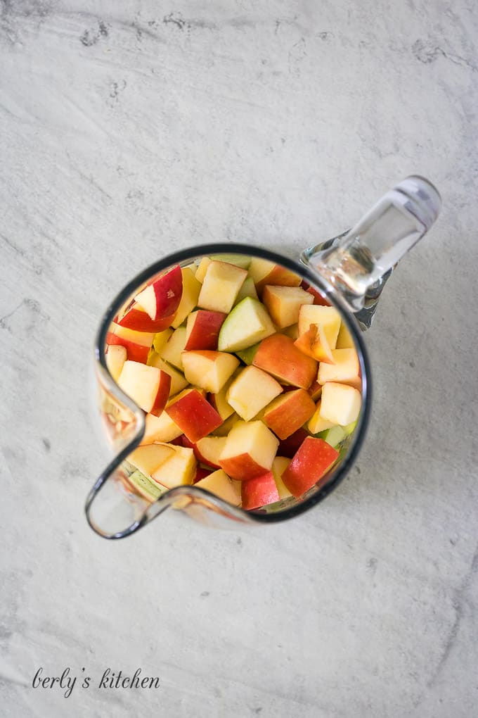 The apples have been diced and placed into a pitcher.