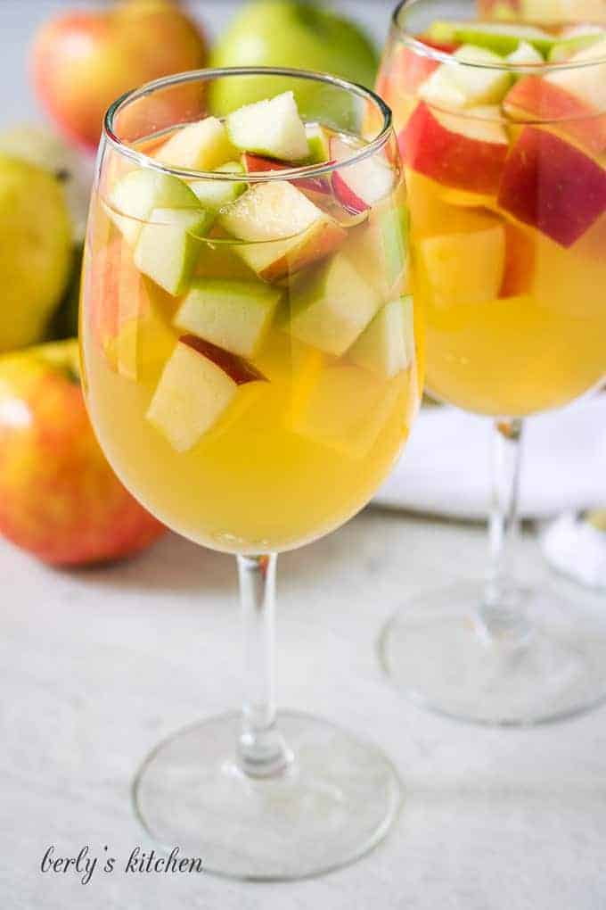 The finished apple sangria poured into two white wine glasses.