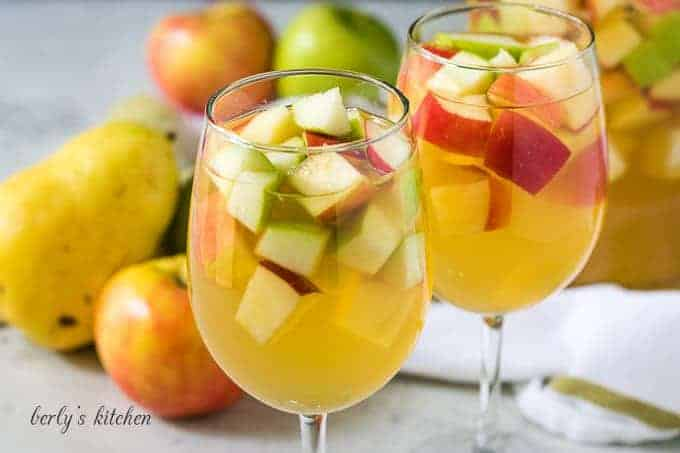 Two glass of apple sangria served in white wine glasses.