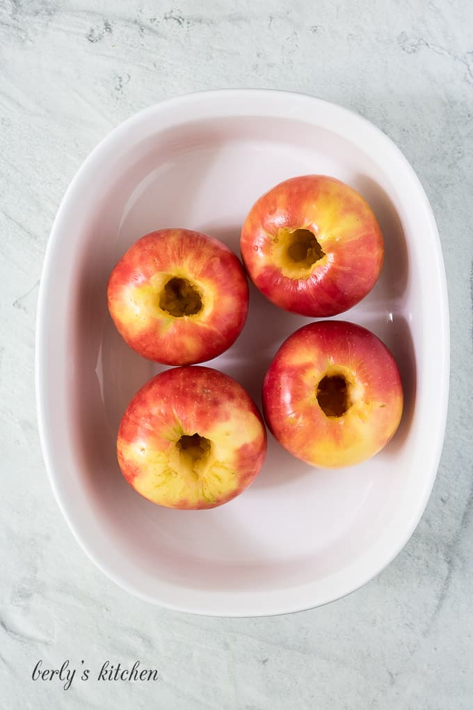 Four washed and cored apples in a large baking dish.