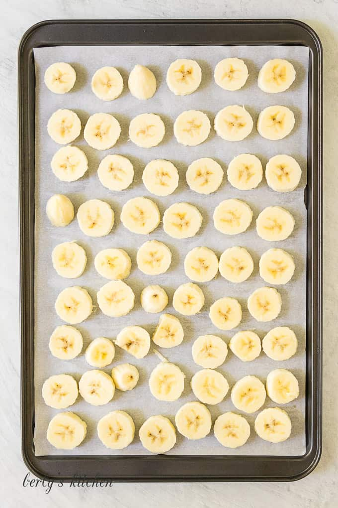 Bananas have been sliced and placed on a sheet pan.