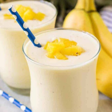 Two finished banana pineapple smoothies garnished with diced fresh pineapple.
