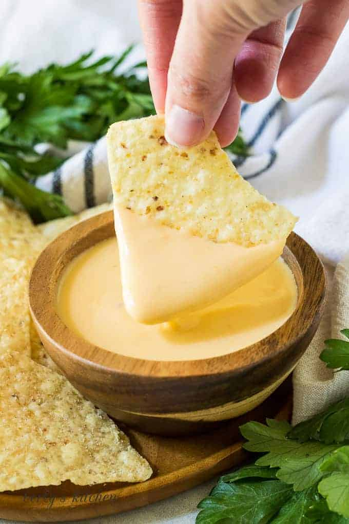 A tortilla chip being dipped into the finished cheese dip.