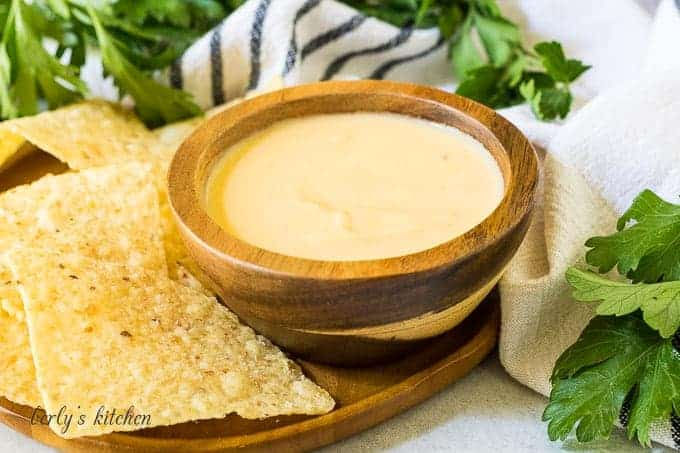 A small wooden bowl of beer cheese dip with chips.