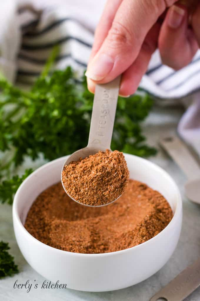 The fajita seasoning mix being lifted from the small bowl.