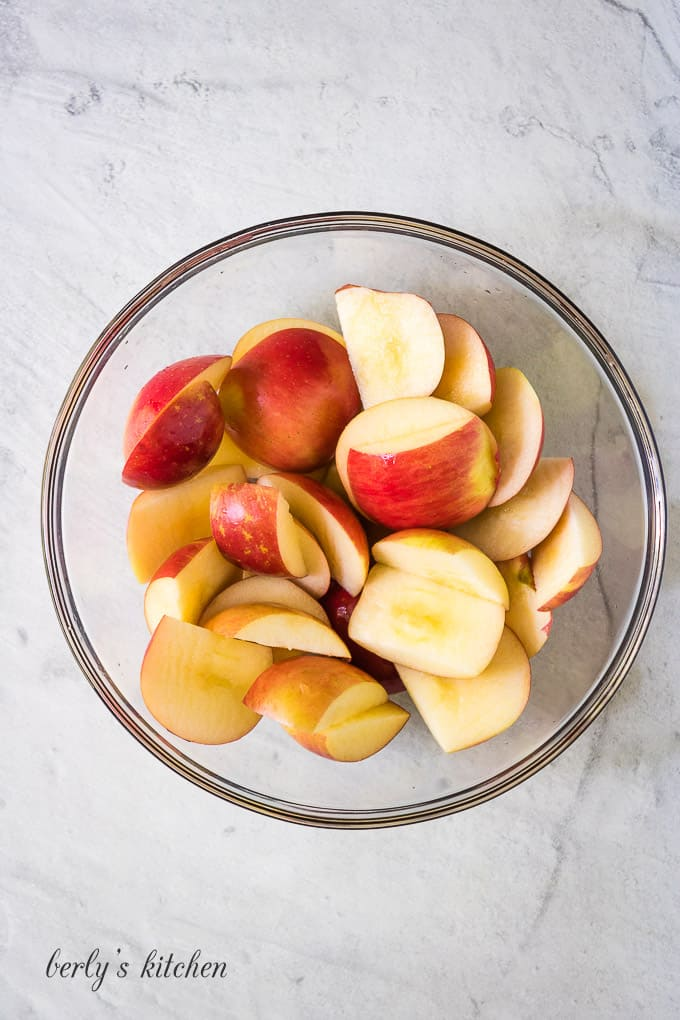 Two pounds of apples, in a bowl, cut into chunks..